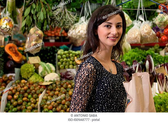 Woman shopping at greengrocer's in market