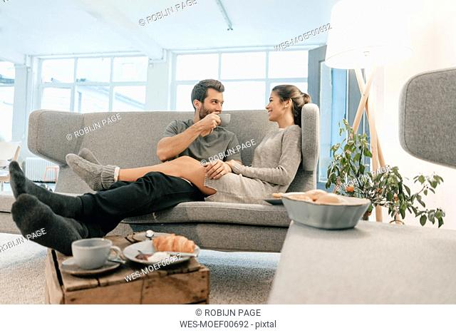 Couple relaxing on couch at home having breakfast