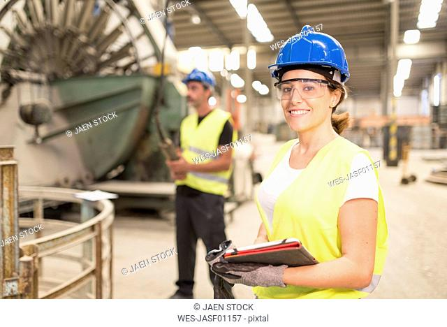 Portrait of smiling woman in factory hall