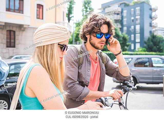 Couple using phone and walking along with push bikes