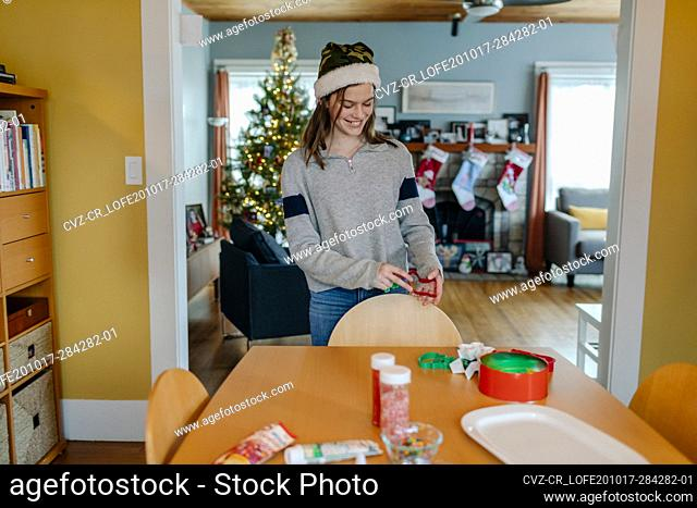 Smiling teenager holding cookie cutters on dinning table at home
