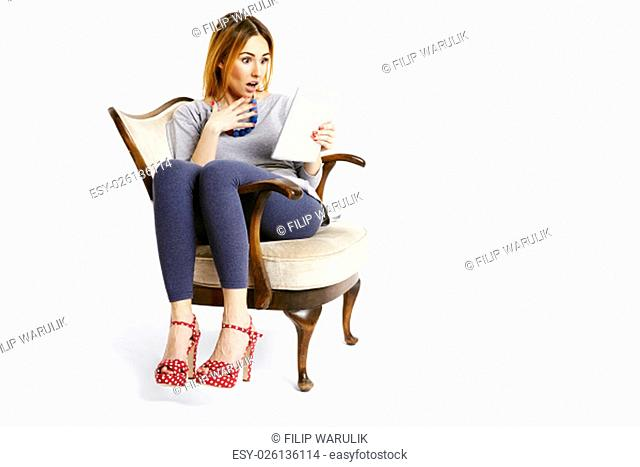 Young woman sitting on a chair with tablet reading e-mails looks very surprised