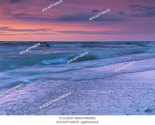 Beautiful tranquil sunset scenery of lake Huron in soft red and blue colors, Pinery Provincial Park, Grand Bend, Ontario, Canada
