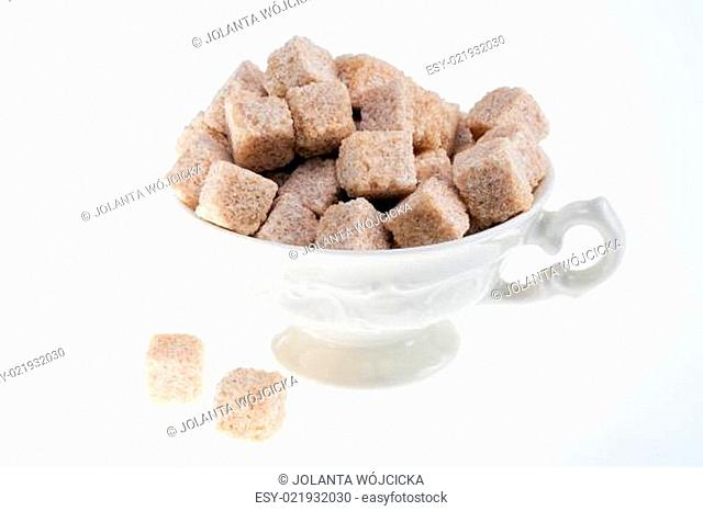 brown sugar cane cubes in porcelalain cup isolated on white background