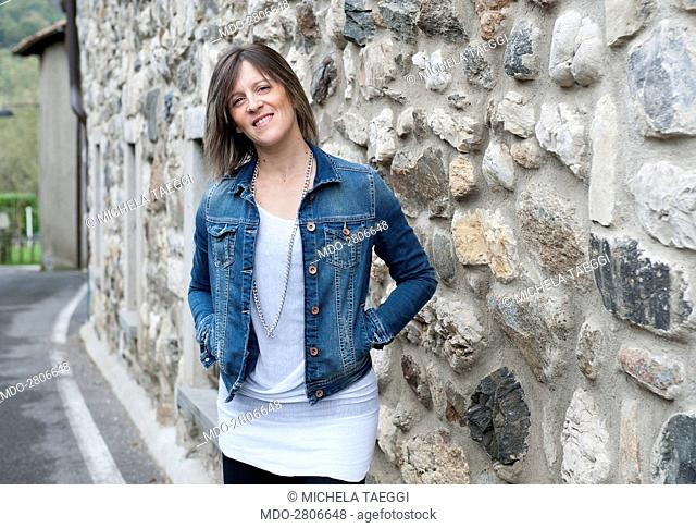 A woman posing in front of a stone outer wall. Caprino Bergamasco (Italy), 15th October 2014