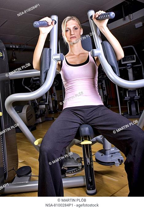 young woman doing strength training in fitness studio