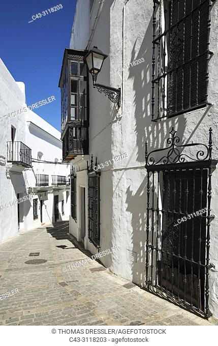 Alleyway and brilliantly whitewashed, reja (grille) fronted houses in the hill-top town of Vejer de la Frontera. Cadiz province, Andalusia, Spain