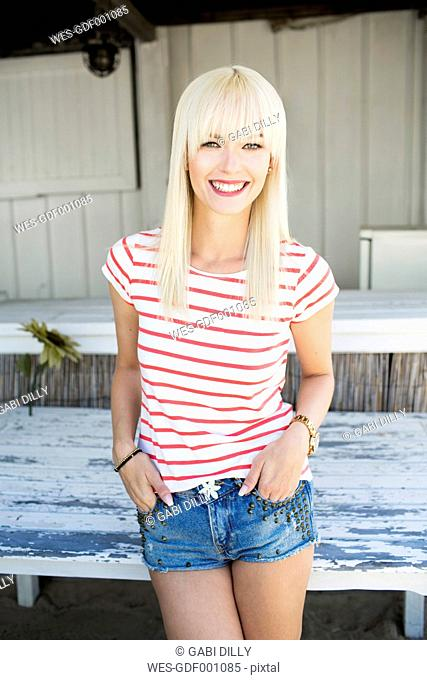 Portrait of smiling blond woman wearing striped t-shirt and Hot Pants