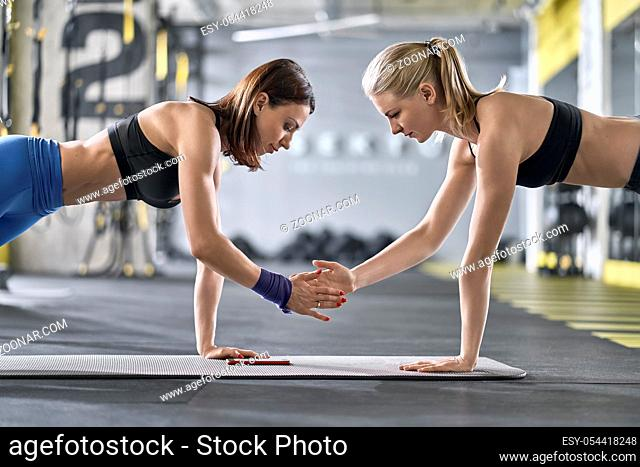 Athletic girls are training on the gray mat in the gym. Women are standing in the plank pose with right hands in the air