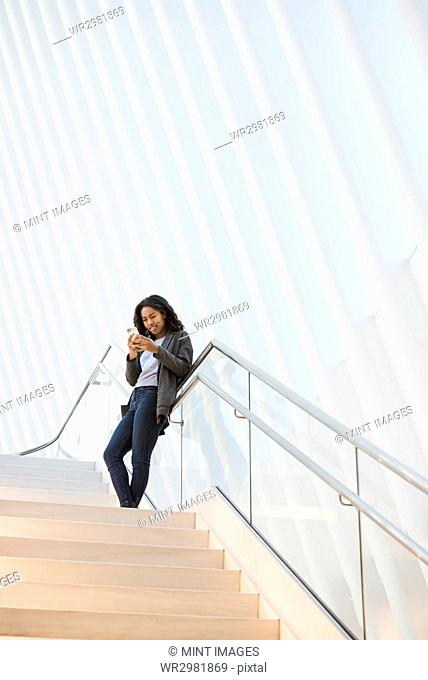 A woman standing on a stairway in the Oculus building at the World Trade Centre under a dramatic ridged white ceiling, checking her phone