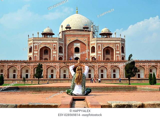 Young woman meditating in the yard of Humayun's Tomb. Delhi, India