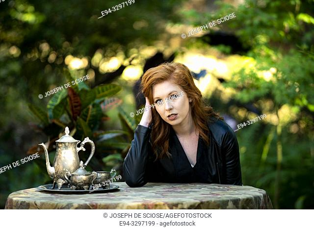 Portrait of a 25 year old redheaded woman in a garden setting