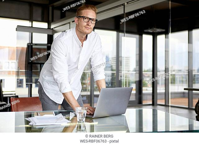 Businessman with laptop on desk in office thinking