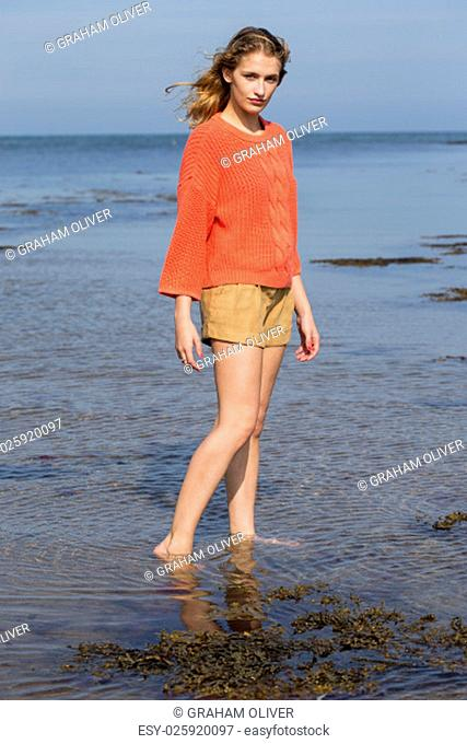Portrait of a beautiful young woman at the beach. She is looking at the camera and wearing casual clothing while standing in the sea