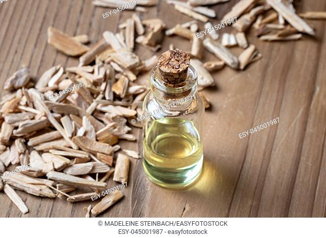 A bottle of essential oil with cedar wood chips and copy space