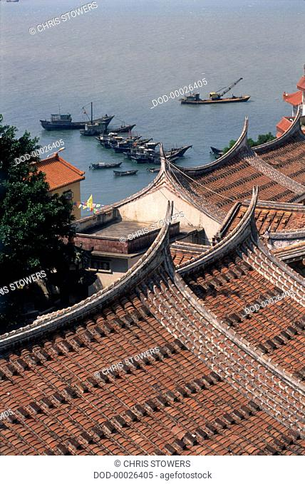 China, Fujian, Meizhou Island, tiled gabled rooftops overlooking moored fishing boats on the shore, elevated view