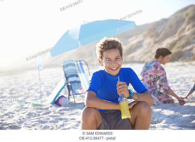 Portrait smiling, confident boy drinking juice on summer sunny beach