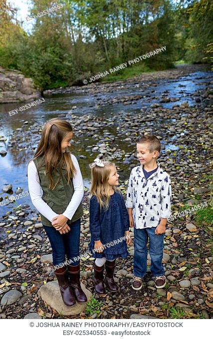 Three kids who are siblings in a candid lifestyle photo outdoors along the banks of the McKenzie River in Oregon