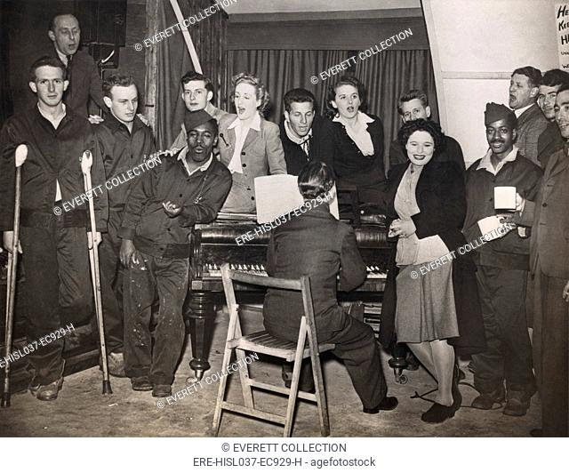 American GIs are entertained by pianist Horatio Davies, at a military hospital in West England. Both black and white soldiers are included in the British ENSA...
