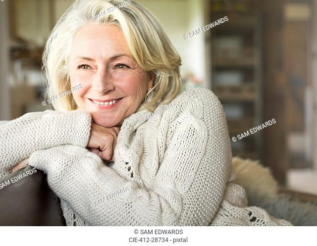 Smiling senior woman in sweater looking away