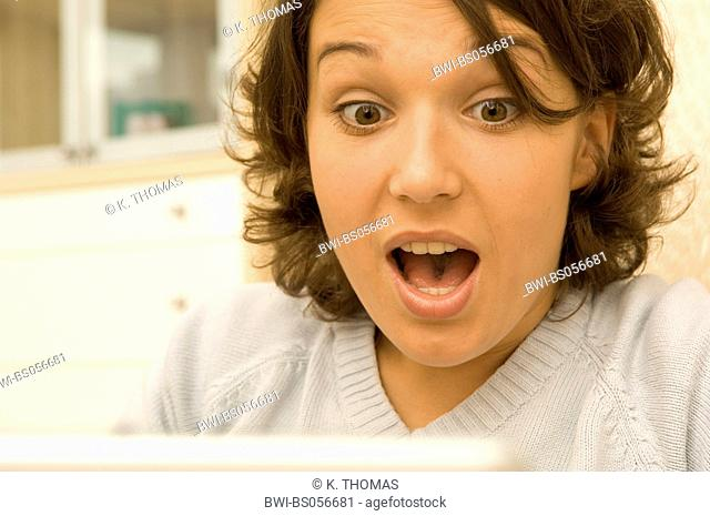 young woman with laptop/notebook, surprised