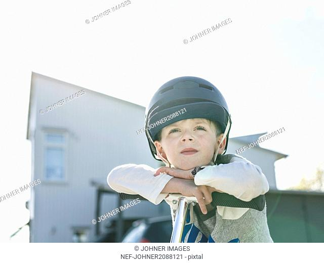 Boy in bicycle helmet standing with kick scooter