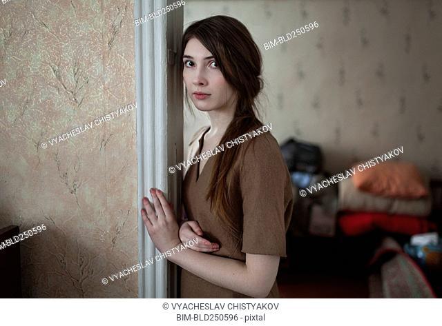 Serious Caucasian woman leaning in doorway