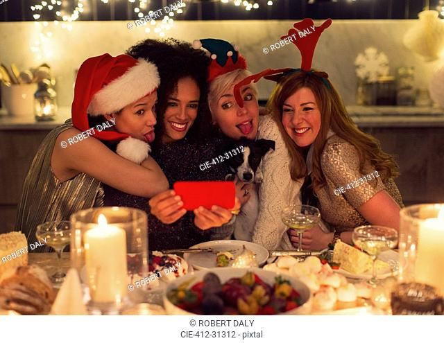 Playful young women with dog taking selfie at Christmas dinner