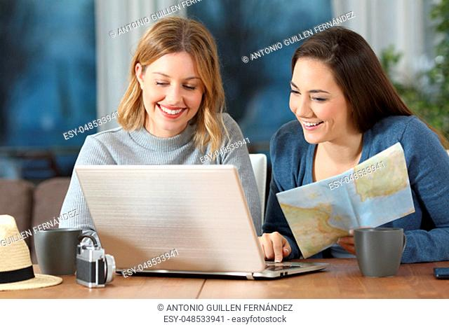 Front view portrait of two happy tourists planning travel in an apartment