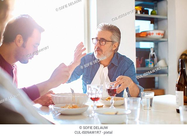 Mature man and adult sons talking at dining table