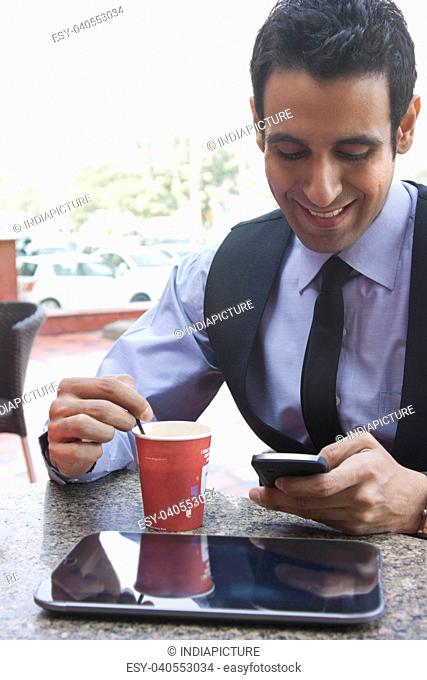 Businessman reading an sms while having coffee , INDIA , DELHI