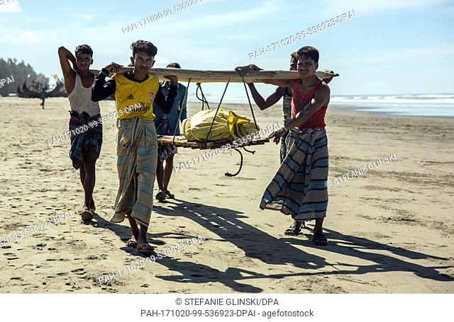 Men carry the body of a Rohingya woman that washed up on a beach near the city of Teknaf, in southern Bangladesh, 10 October 2017