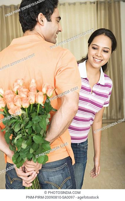 Man hiding a bouquet of roses from his girlfriend