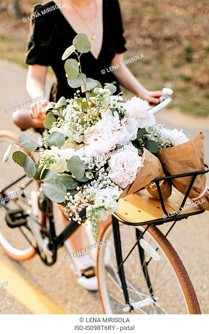 Young woman pushing bicycle with bunch of flowers on rural road, neck down, Menemsha, Martha's Vineyard, Massachusetts, USA