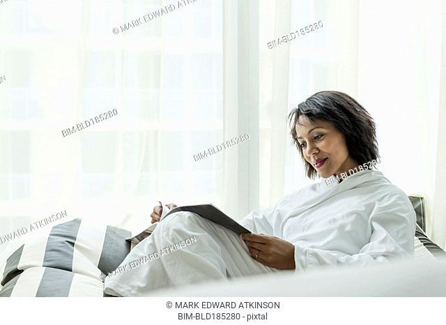 African American woman reading magazine near window