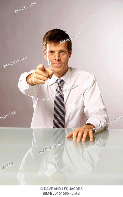Caucasian businessman pointing from table