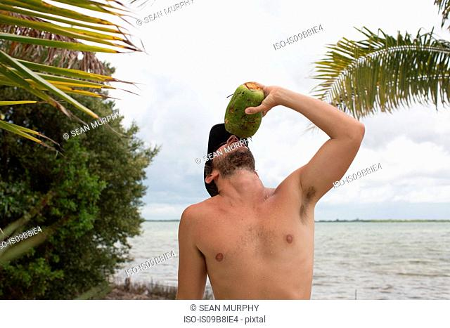 Man beside water drinking from coconut
