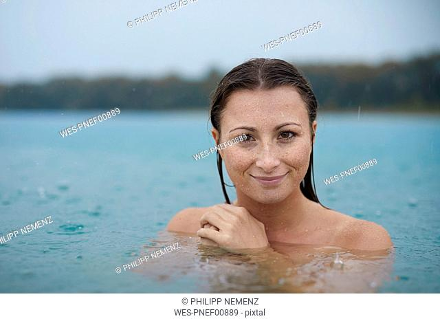 Portrait of smiling young woman bathing in lake on rainy day