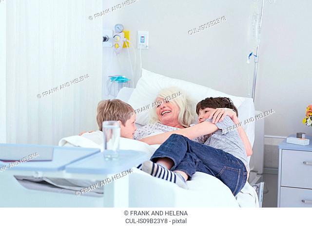 Senior female patient cuddling grandsons on hospital bed