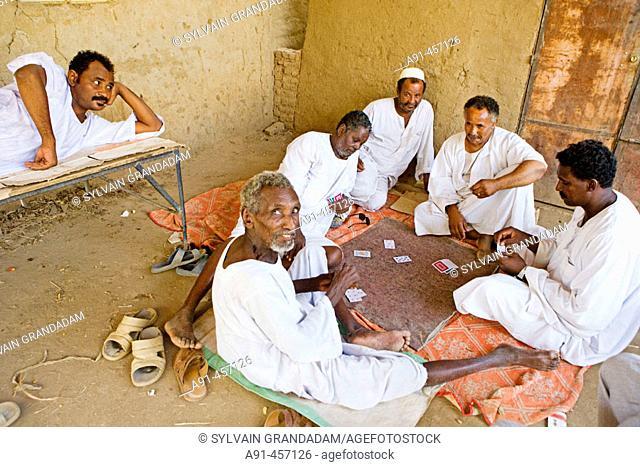 Men playing cards in the village of Dalgo. Upper Nubia, ash-Shamaliyah state, Sudan