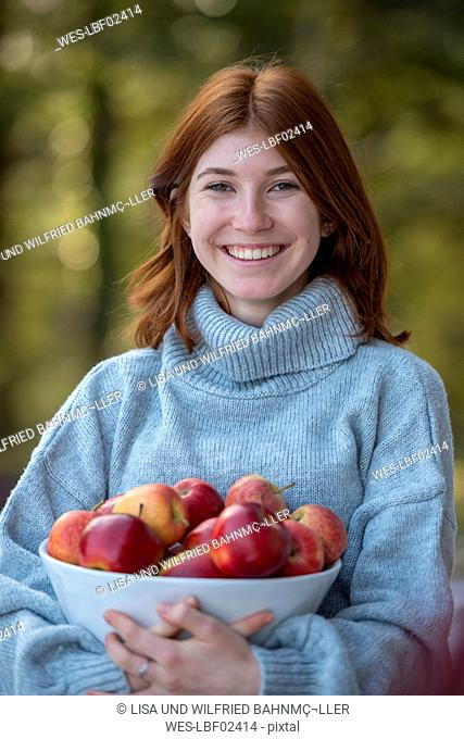 Portrait of happy redheaded teenage girl holding bowl of apples