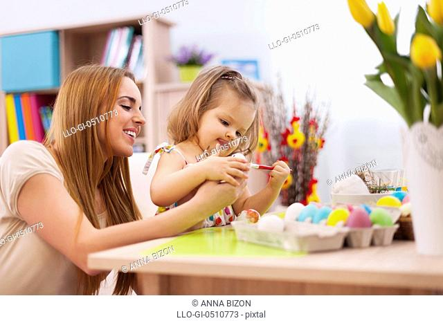 Focus little girl painting easter eggs with mother. Debica, Poland