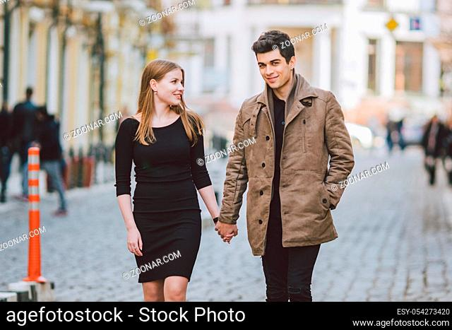 Urban modern young love couple walking romantic talking talking, holding hands on a date. Young multicultural Turkish brunette and Caucasian couple on old...