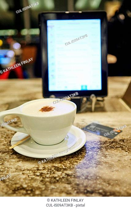 Cup of coffee, digital tablet and credit card on restaurant table