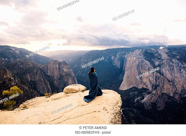 Young woman wrapped in blanket, standing at top of mountain, overlooking Yosemite National Park, California, USA