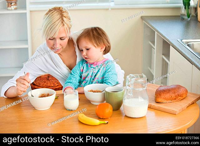 Mother and cute daughter having breakfast