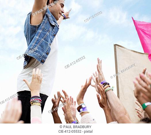 Performer standing above cheering crowd at music festival