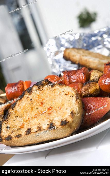 Plate with grilled bread, fruit and sausage
