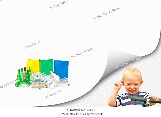 Smiling blond boy is looking at a camera next to the pile of sorted waste with ready colored bags on the white background ready for your text