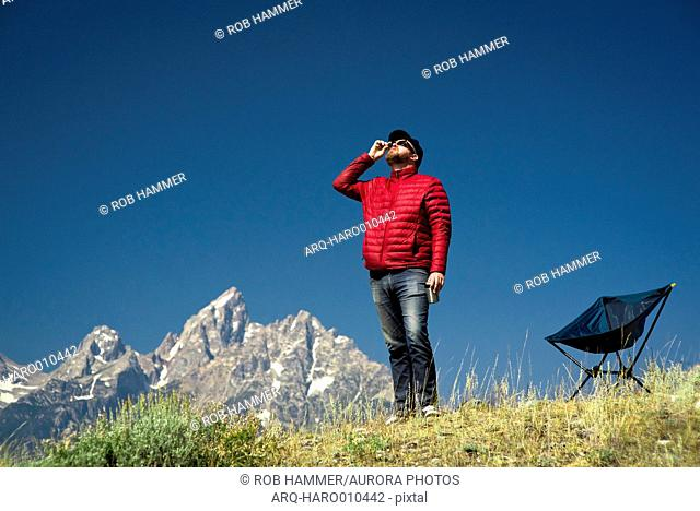 Man looking up at sky while watching solar eclipse, Teton Mountains in background, Jackson Hole, Wyoming, USA